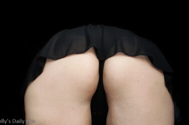 Molly bending over in short skirt and black knickers for a story about a quickie