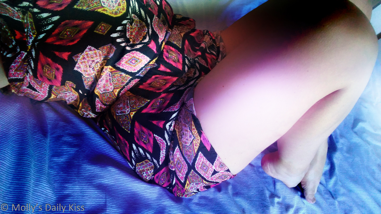 woman laying on bed wearing colourful summer dress for a first date