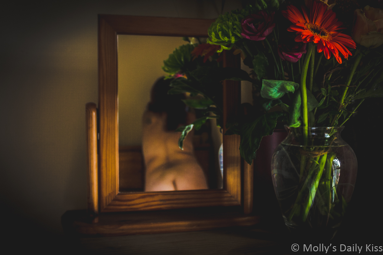 Flowers by mirror with mollys back and bum relfected in the glass