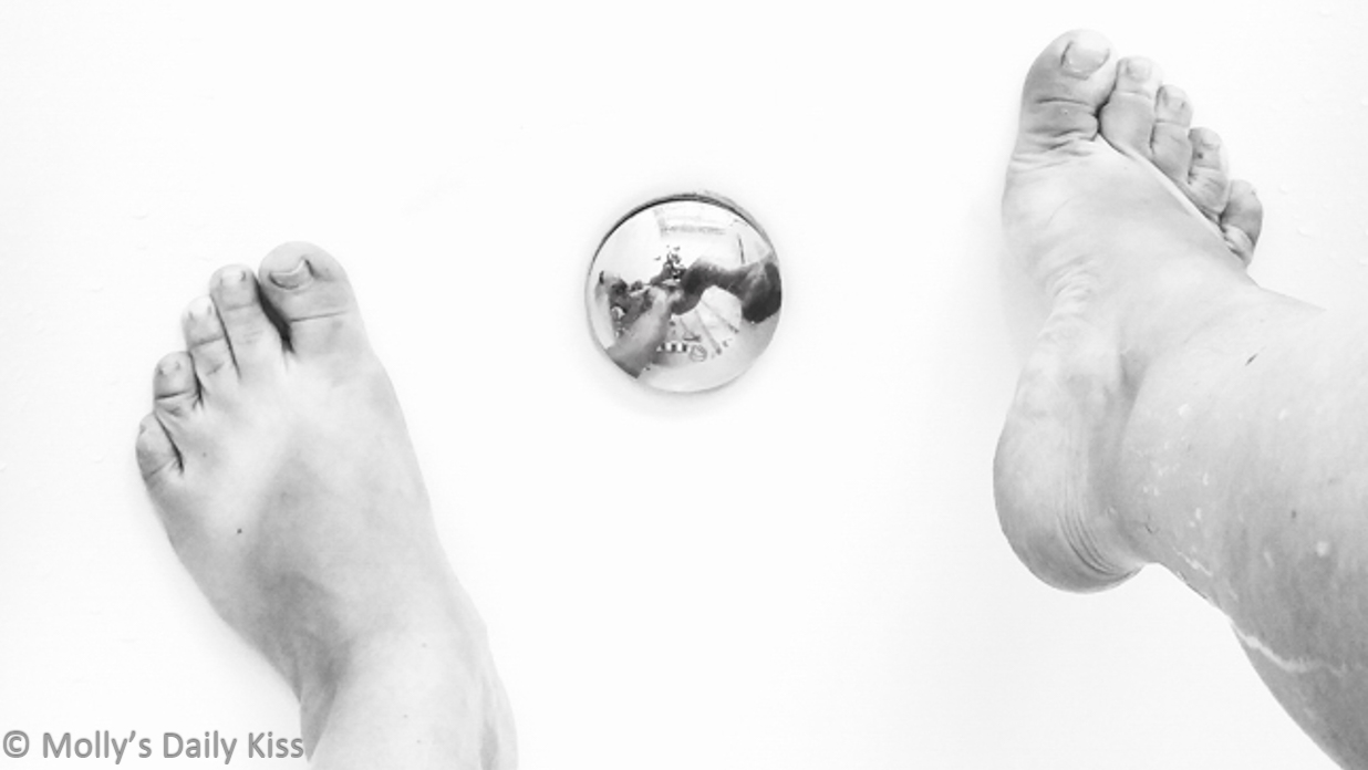 Mollys feet in the shower with her naked body reflected in the plug