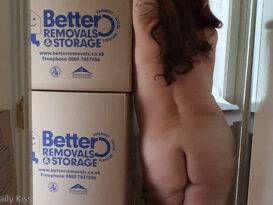 Cropped image of molly naked leaning against moving boxes