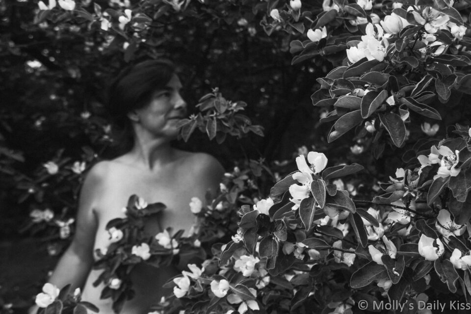 Molly standing naked in blossom tree edited in bacl and white for post about change