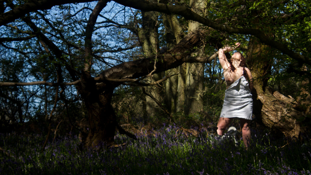 Molly is a girl and her dog in bluebell woods with her dress down baring her breast with a dog at her feet