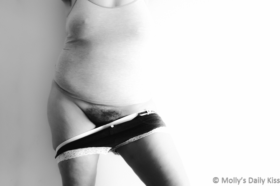 Molly standing up against the wall with panties half pulled down to show of her bush pubes in black and white for post called now or never