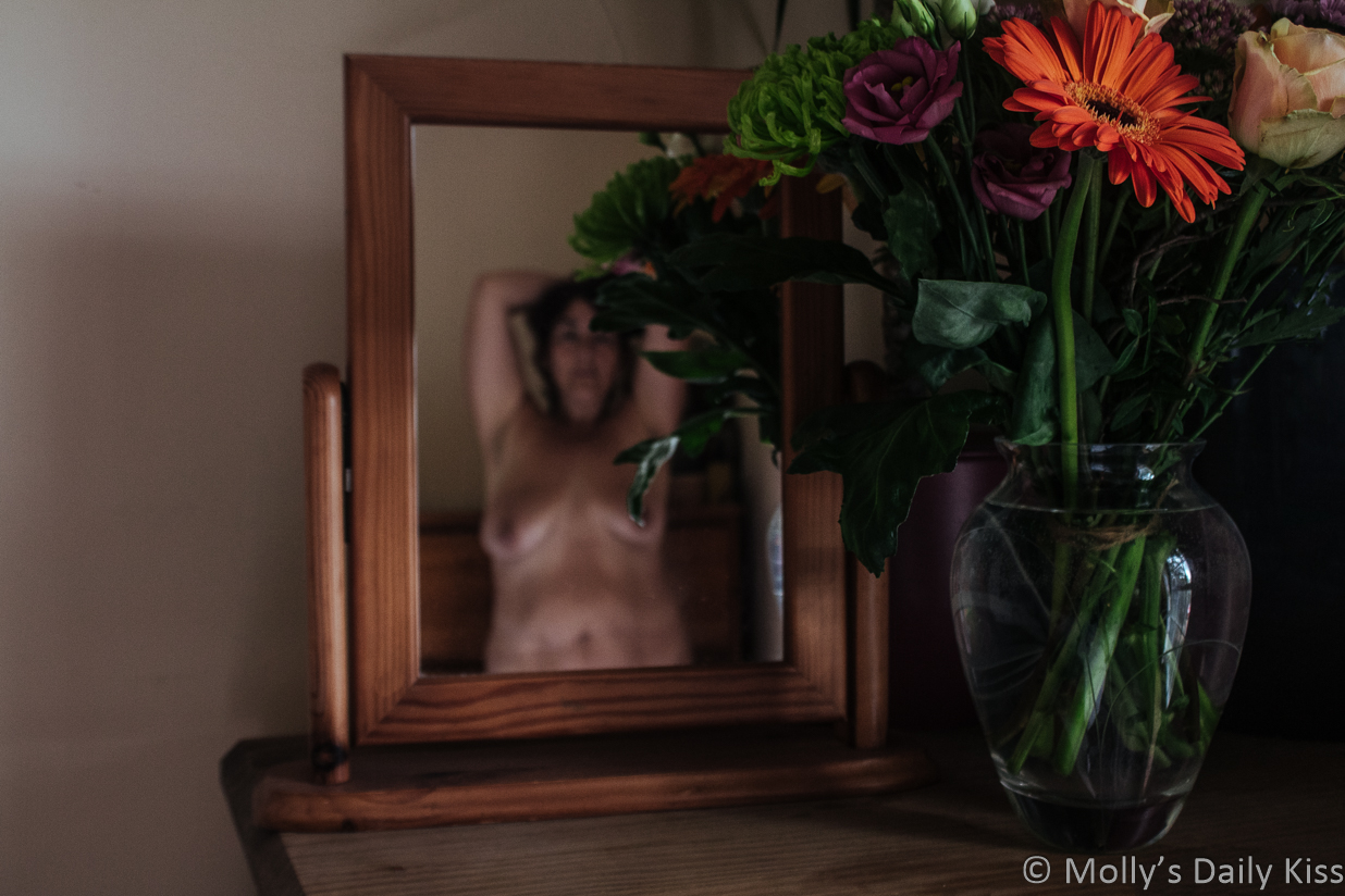 Molly topless reflected in mirror with vase of flowers next to mirror for post about serve you