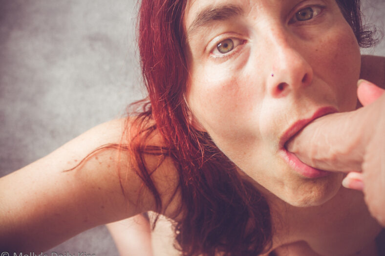 Molly with realistic cock dildo in her mouth looking up at the camera