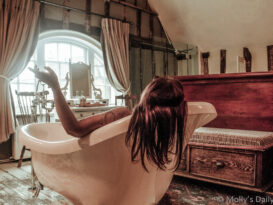 Molly siitting in a big clawfoot bath in the middle of a hotel room