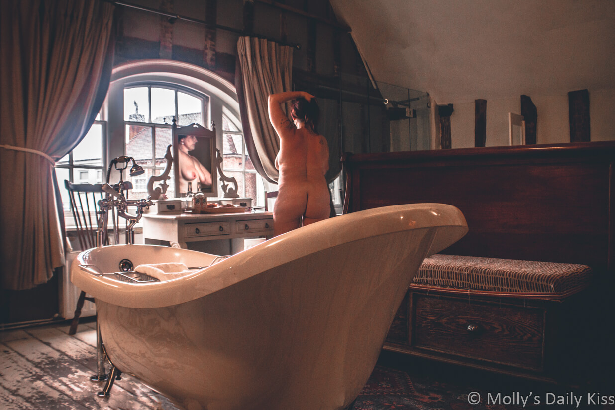 Molly naked in hotel room with bath in middle of the room and her breasts refelcted in the vanity mirror for post called aphrodisiac quality