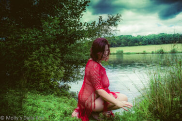 Molly wearing red fishnet shawl and kneeling down by lake for post called order