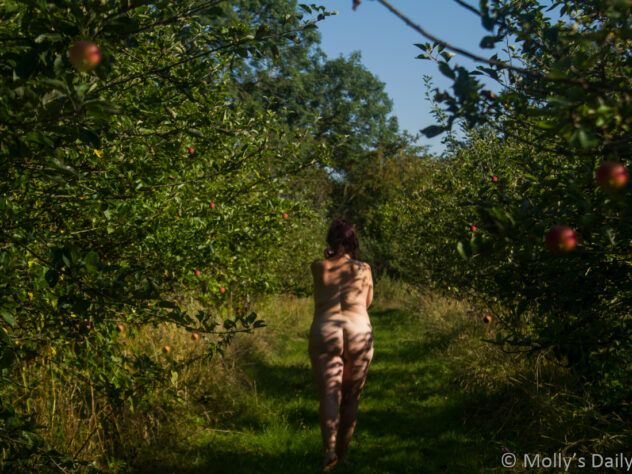 Molly walking naked through apple orchard