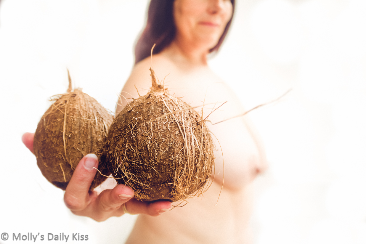 Molly standing topless holding coconuts for post called I've got a lovely bunch of coconuts