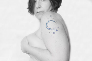 Molly looking over her shoulder at the camera cupping her breasts and showing off the moon and stars tattoo on her bicep