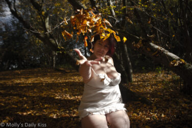 Molly sitting in woods in white lingerie throwing up handful of golden autumn leaves