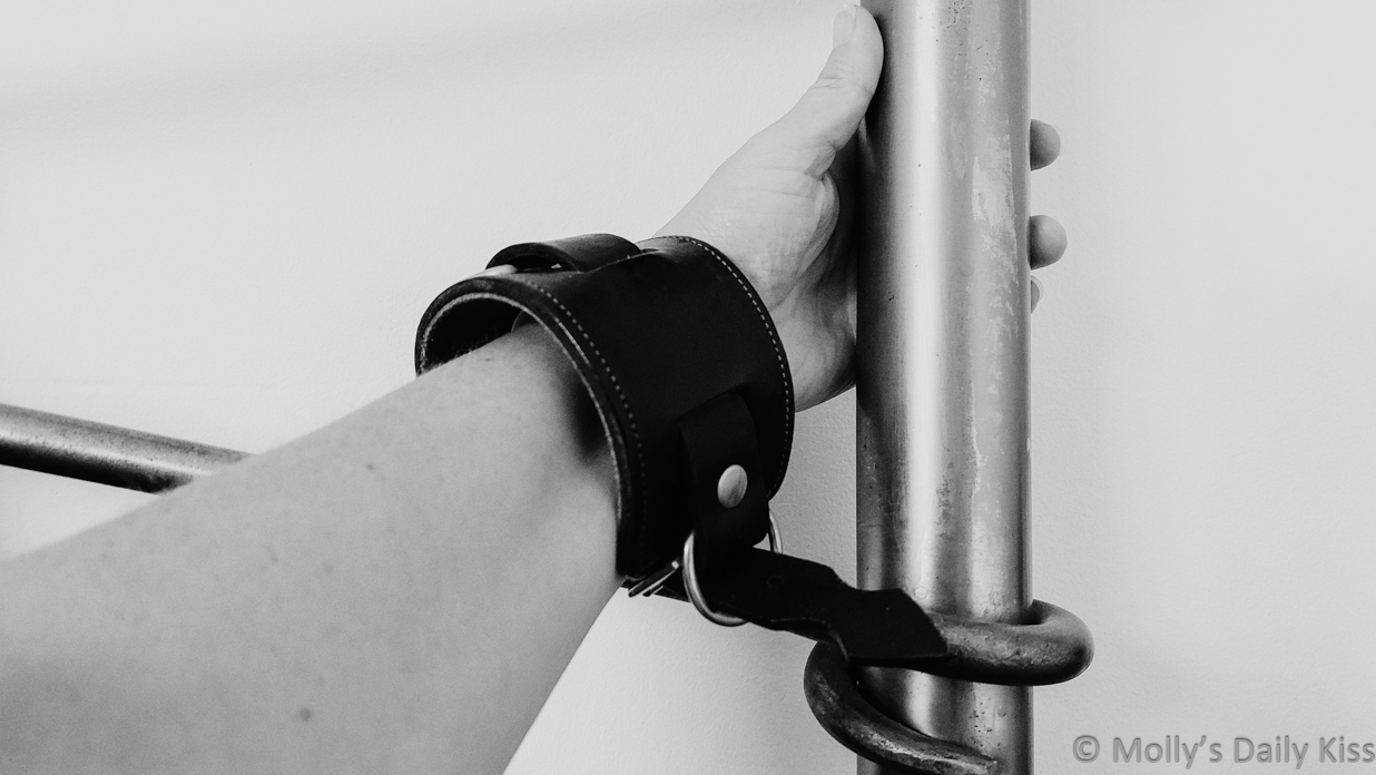 Molly's arm and wrist cuffed to the metal bedframe for post about tickle fetish