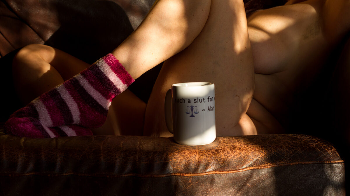 Molly sitting in the sunshine on the sofa wearing stripped socks with mug that says slut on it